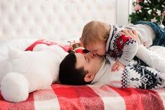 逗人喜爱的愉快的父亲和儿子画象圣诞节的在床上 免版税库存照片