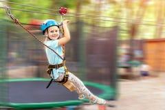逗人喜爱的矮小的滑稽的盔甲的caucasion白肤金发的女孩有乐趣骑马绳索zipline在冒险公园 儿童室外极限运动 免版税库存图片