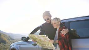 逗人喜爱的行家夫妇在汽车前面站立,看路线图享有青年时期和生活本质上 移动式摄影车射击 股票视频