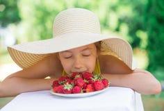 逗人喜爱的青春期前的女孩画象大帽子的吃着草莓夏日 图库摄影