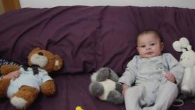 逗人喜爱的4个月紫色卧具的男婴与兔宝宝玩具 股票录像