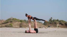 适合的运动的与伙伴的夫妇实践的acro瑜伽一起在沙滩 影视素材