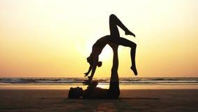 适合的运动的与伙伴的夫妇实践的acro瑜伽一起在沙滩 股票录像