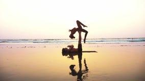 适合的运动的与伙伴的夫妇实践的acro瑜伽一起在沙滩 股票视频