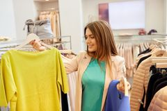 选择衣裳的愉快的妇女在服装店 免版税图库摄影