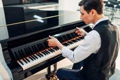 钢琴演奏家打开大平台钢琴键盘盒盖  免版税库存照片