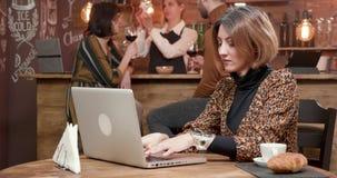 键入在她的膝上型计算机的年轻女商人一则重要消息,当在coffe商店时 股票录像