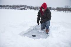 钓鱼在一个湖的中间年迈的人冰在明尼苏达在冬天期间 库存照片