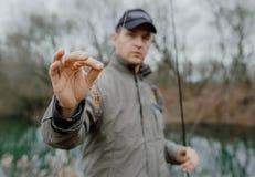 钓鱼拿着诱饵的人 免版税库存照片