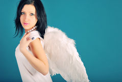 É uma menina bonita em um papel do anjo em um azul Imagens de Stock