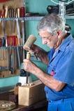 Ébéniste découpant le bois avec un burin et un marteau Image stock