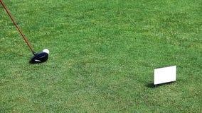 Ébrèchement d'une boule de golf sur le vert avec le club de golf photographie stock