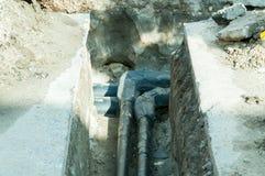 Écartez le tuyau d'un coup de coude du réseau de pipe-lines souterrain de chauffage urbain dans le fossé image libre de droits