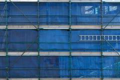 Échafaudage et palissades bleues avec l'échelle sur le chantier de construction Image libre de droits