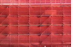 Échafaudage sur un site de construction de bâtiments couvert de FAS rouge Photo libre de droits