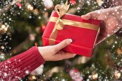 Échange de cadeau d'homme et de femme avec la frontière de flocons de neige Photo libre de droits