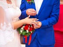 Échange des anneaux les jeunes mariés Photo stock