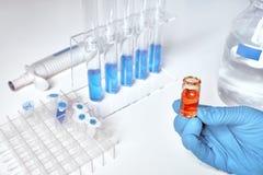 Échantillon liquide dans la main femelle, échantillons liquides bleus dans des tubes de verre images libres de droits