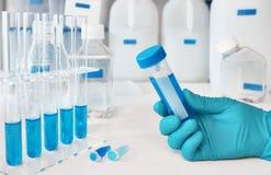 Échantillon liquide dans la main femelle enfilée de gants, échantillons liquides bleus dans les glas photographie stock libre de droits