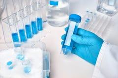 Échantillon liquide dans la main femelle enfilée de gants, échantillons liquides bleus dans les glas photographie stock