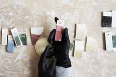 Échantillons d'émail coloré pour la couleur en céramique dans des mains, processus fonctionnant dans le studio, argile, bois, mét Photo libre de droits