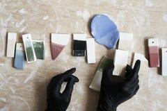 Échantillons d'émail coloré pour la couleur en céramique dans des mains, processus fonctionnant dans le studio, argile, bois, mét Images libres de droits