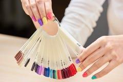 Échantillons de couleurs de clous dans des mains femelles Photo libre de droits