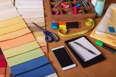 Échantillons de tissu, accessoires de couture, bloc-notes sur le bureau Images libres de droits