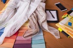 Échantillons de tissus, de bloc-notes et de stylo sensibles minces sur le bureau Photo libre de droits
