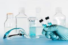 Échantillons liquides dans la main enfilée de gants, laboratoire images libres de droits