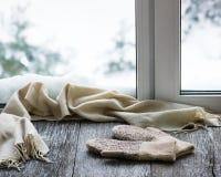 Écharpe beige et mitaines de laine situées sur le filon-couche en bois de fenêtre Images libres de droits