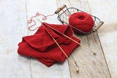 Écharpe, boule de fil et aiguilles de tricotage rouges tricotées à la main Photos libres de droits