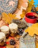 Écharpe de chapeau et bonbons naturels à miel dans des pots près de tasse de feuilles tombées couvertes par fond de thé Festins f image stock
