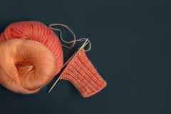 Écharpe de mohair de mélange, boule de fil et aiguilles de tricotage colorées oranges de tricotage lumineuses Le début du tissu d Photo stock