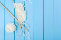 Écharpe et chapeau blancs tricotés sur le fond en bois bleu Photos libres de droits