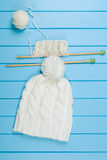 Écharpe et chapeau blancs tricotés sur le fond en bois bleu Images stock