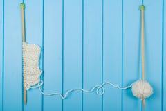 Écharpe et chapeau blancs tricotés sur le fond en bois bleu Photographie stock