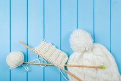 Écharpe et chapeau blancs tricotés sur le fond en bois bleu Photographie stock libre de droits