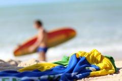 Écharpe froissée et surfer brouillé sur une plage Photos libres de droits