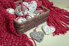 Écharpe rouge tricotée par laine naturelle Décorations de Noël sous forme de boules et en forme de coeur Photos stock