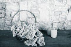 Écharpe tricotée dans le panier et bougie de couleur sur l'opp en bois de table Images stock