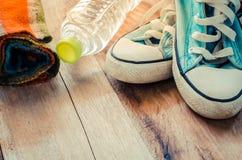 Écharpes accessoires, chaussures, bouteilles d'eau placées sur un plancher en bois Photos libres de droits