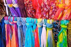 Écharpes brillamment colorées sur l'armoire Photographie stock