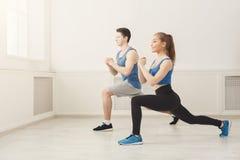 Échauffement de couples de forme physique étirant la formation à l'intérieur Image libre de droits