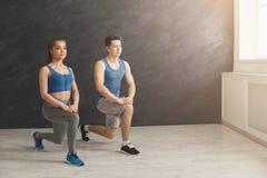 Échauffement de couples de forme physique étirant la formation à l'intérieur Images libres de droits
