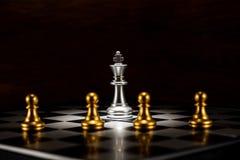 Échecs argentés simples de roi entourés par un certain nombre de PA d'échecs d'or Images stock