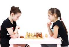 Échecs de jeu de deux écolières sur le fond blanc Photographie stock