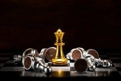 Échecs de reine d'or entourés par un certain nombre d'échecs argentés tombés p photographie stock libre de droits