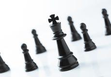 Échecs noirs de roi devant l'équipe au-dessus du fond blanc Images stock