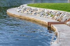 Échelle argentée de piscine près de lac Photographie stock libre de droits